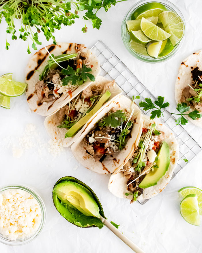 Flatlay of Grilled Chicken Tacos with optional garnishes.