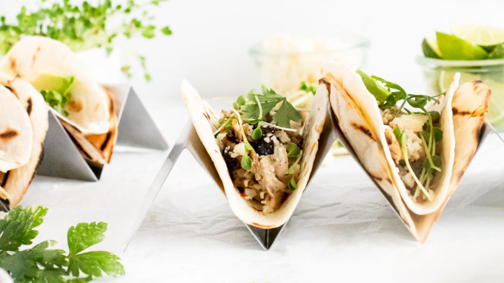 Horizontal view of tacos to show grill marks and green garnishes.