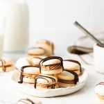 Stacked macarons on a while plate surrounded by a milk jug and chocolate chips.